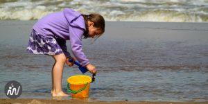 Enfant qui cherche attentivement des trésors dans la mer