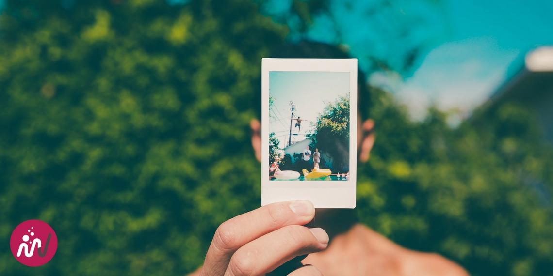 portrait d'un homme qui montre une photo avec des souvenirs au lieu de son visage